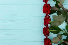 Frontière de roses rouges, fond en bois coloré Photos libres de droits