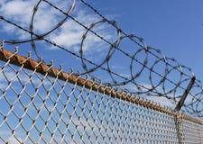 Frontière de sécurité de barbelé contre le ciel bleu Photographie stock libre de droits