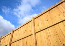 Frontière de sécurité en bois contre un ciel nuageux Image libre de droits