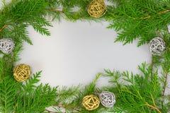 Frontière des branches à feuilles persistantes avec des boules de brindille d'argent et d'or photos libres de droits