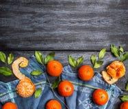 Frontière des mandarines avec des feuilles sur le fond en bois rustique bleu Photographie stock libre de droits