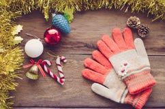 Frontière et gants de Noël oranges sur le bois - modifiez la tonalité le vintage photographie stock libre de droits