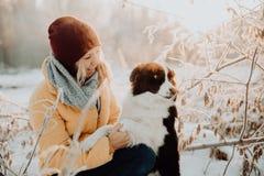 Frontière noire et blanche mignonne pelucheuse adorable colly étant qualifiée et choyant la fille en parc lumières et buissons su photos stock