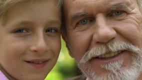 Fronti del nonno e del nipote che guardano in camera e che sorridono, foto di famiglia video d archivio