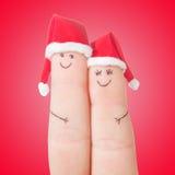 Fronti delle dita in cappelli di Santa Coppie felici che celebrano concetto Fotografia Stock