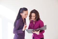 Fronti delle ragazze di affari con i documenti di una cartella Immagini Stock