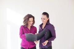 Fronti delle ragazze di affari con i documenti di una cartella Immagini Stock Libere da Diritti