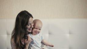 Fronti di risata della famiglia felice, madre che tiene il neonato adorabile del bambino, sorridente ed abbracciante, confine alt stock footage