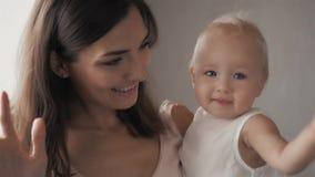 Fronti di risata della famiglia felice, madre che tiene il neonato adorabile del bambino, sorridente ed abbracciante, confine alt archivi video