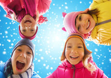 Fronti felici dei piccoli bambini sopra cielo blu e neve Immagine Stock