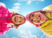 Fronti felici delle bambine sopra cielo blu Fotografie Stock