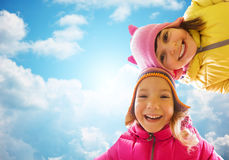 Fronti felici delle bambine sopra cielo blu Fotografia Stock Libera da Diritti