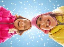 Fronti felici delle bambine sopra cielo blu e neve Fotografie Stock Libere da Diritti
