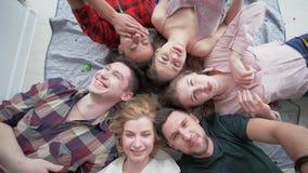 Fronti felici, punto di vista superiore degli amici allegri che si trovano insieme su di gomma da masticare di salto della parte