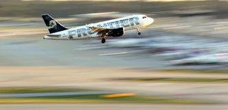 Frontier airplane in motion flying. A Frontier airlines plane has just taken off from the runway , landing gear still down, with blurred background, during royalty free stock photo