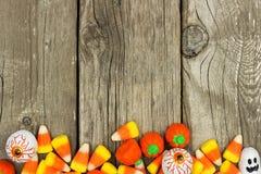 Frontière du fond de sucrerie de Halloween contre le bois rustique Images stock