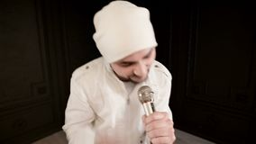 Frontman vocalist rock pop with a stylish beard in white clothes and a hat with a microphone in his hands expressively. Aggressively singing in the studio stock footage