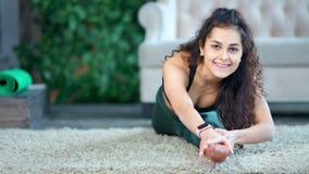 Frontowego widoku brunetki urocza uśmiechnięta kędzierzawa dziewczyna robi sportom ćwiczy pokazywać zadziwiającego rozciąganie zbiory
