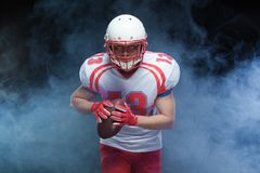 Frontowego widoku portret jest ubranym hełm z piłką przeciw bielu dymowi futbolu amerykańskiego gracz zdjęcie royalty free