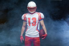 Frontowego widoku portret jest ubranym hełm z piłką przeciw bielu dymowi futbolu amerykańskiego gracz zdjęcia royalty free