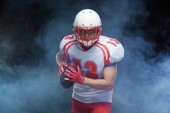 Frontowego widoku portret jest ubranym hełm z piłką przeciw bielu dymowi futbolu amerykańskiego gracz obrazy stock