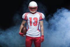 Frontowego widoku portret jest ubranym hełm z piłką przeciw bielu dymowi futbolu amerykańskiego gracz fotografia royalty free