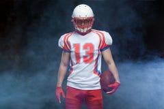 Frontowego widoku portret jest ubranym hełm z piłką przeciw bielu dymowi futbolu amerykańskiego gracz obrazy royalty free
