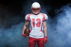 Frontowego widoku portret jest ubranym hełm z piłką przeciw bielu dymowi futbolu amerykańskiego gracz zdjęcia stock