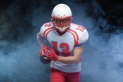 Frontowego widoku portret jest ubranym hełm z piłką przeciw bielu dymowi futbolu amerykańskiego gracz obraz stock
