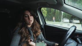 Frontowego widoku zakończenia brunetki młoda kobieta pięknych kędziory Piękny makeup siedzi w jej samochodzie w parking, chce zbiory wideo