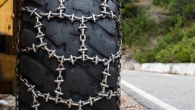 Frontowy ładowacz dla śnieżnego usunięcia z metali śnieżnymi łańcuchami na kołach Śnieżny usunięcie w górach zdjęcie royalty free