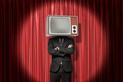Frontowy uprawa wizerunek mężczyzna w kostiumu z rękami składać zamiast z telewizor głową i, stoi w światło reflektorów przy czer zdjęcia royalty free