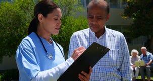Frontowy widok aktywna Azjatycka starszego mężczyzny i kobiety lekarka dyskutuje nad raportem medycznym w ogródzie zbiory