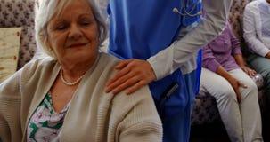 Frontowy widok aktywna starsza kobiety mienia ręka kobiety lekarka przy karmiącym domem 4k zbiory