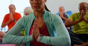 Frontowy widok aktywnej rasy starszy ludzie z trenera spełniania joga w sprawności fizycznej studiu 4k zbiory