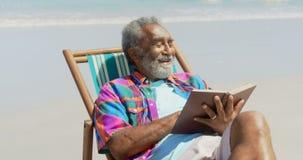 Frontowy widok aktywny starszy amerykanin afrykańskiego pochodzenia mężczyzna czyta książkę na deckchair przy plażą 4k zdjęcie wideo
