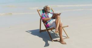 Frontowy widok aktywny starszy amerykanin afrykańskiego pochodzenia mężczyzna relaksuje na deckchair z książką na plaży 4k zbiory