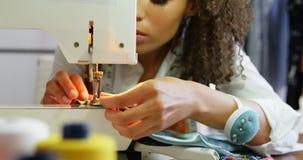 Frontowy widok amerykanin afrykańskiego pochodzenia żeński projektant mody pracuje z szwalną maszyną w warsztacie 4k zbiory