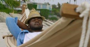 Frontowy widok amerykanin afrykańskiego pochodzenia mężczyzny dosypianie w hamaku na plaży 4k zdjęcie wideo