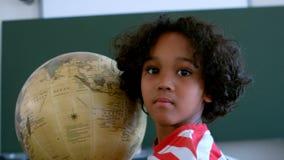 Frontowy widok amerykanin afrykańskiego pochodzenia uczeń z kulą ziemską w sali lekcyjnej przy szkołą zdjęcie wideo