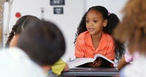 Frontowy widok amerykanin afrykańskiego pochodzenia uczennicy nauczania schoolkids w sali lekcyjnej 4k zbiory wideo