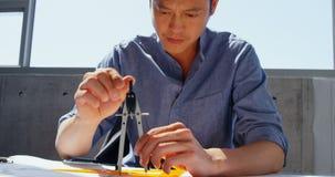 Frontowy widok Azjatycki męski architekt pracuje na projekcie przy biurkiem w nowożytnym biurze 4k zdjęcie wideo
