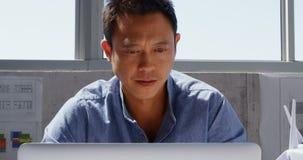 Frontowy widok Azjatycki męski architekt używa laptop na biurku w nowożytnym biurze 4k zbiory