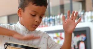 Frontowy widok baczny Azjatycki uczniowski bawić się bongo w sali lekcyjnej przy szkołą 4k zbiory wideo