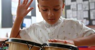 Frontowy widok baczny Azjatycki uczniowski bawi? si? bongo w sali lekcyjnej przy szko?? 4k zbiory wideo