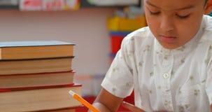 Frontowy widok baczny Azjatycki uczniowski studiowanie przy biurkiem w sali lekcyjnej przy szkołą 4k zbiory