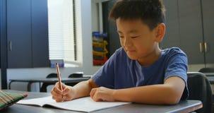 Frontowy widok baczny Azjatycki uczniowski studiowanie przy biurkiem w sali lekcyjnej przy szko?? 4k zbiory