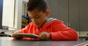 Frontowy widok baczny Azjatycki uczniowski studiowanie z cyfrową pastylką w sali lekcyjnej przy szkołą 4k zbiory