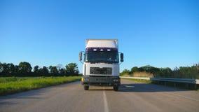 Frontowy widok ciężarówka z ładunek przyczepy jeżdżeniem na autostrady odtransportowania towarach przy letnim dniem Biała ciężaró zbiory