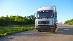 Frontowy widok ciężarówka z ładunek przyczepy jeżdżeniem na autostrady odtransportowania towarach przy słonecznym dniem Ciężarówk zdjęcie wideo